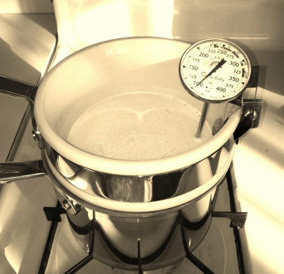 Double boiler with milk and thermometer